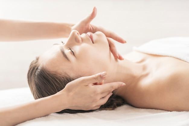 Mulher jovem fazendo massagem na cabeça no salão de beleza
