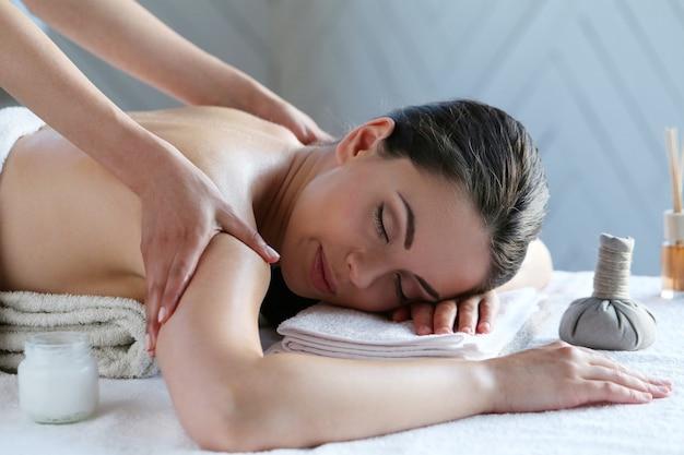 Mulher jovem fazendo massagem nas costas e ombros