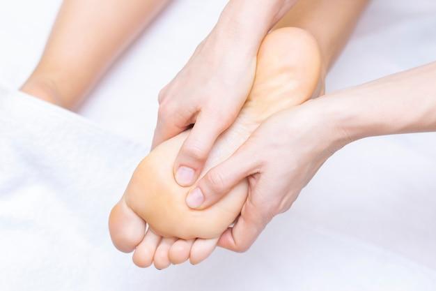 Mulher jovem fazendo massagem nos pés no salão de beleza, vista de perto