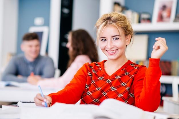 Mulher jovem, fazendo notas, em, estudo, sala