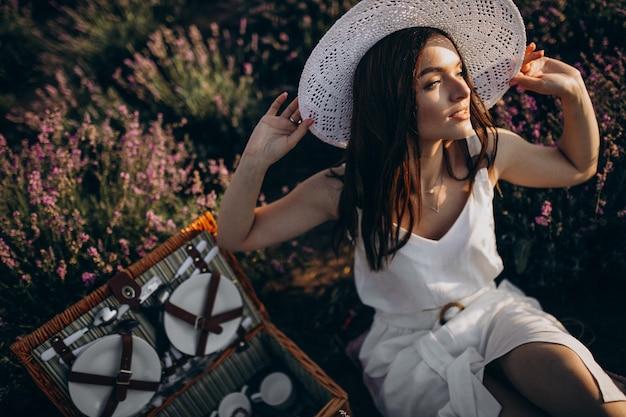 Mulher jovem fazendo piquenique em um campo de lavanda