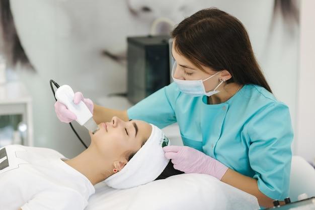 Mulher jovem fazendo procedimento de beleza em salão de spa