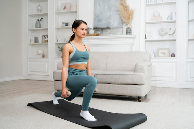 Mulher jovem fazendo seu treino em casa em uma esteira de ginástica