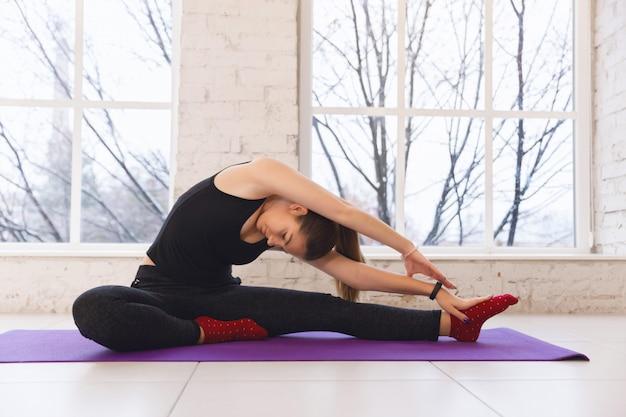 Mulher jovem, fazendo, stratching, para, pernas, em, ioga posa
