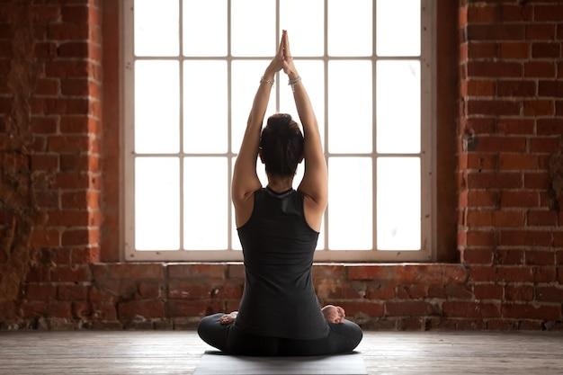 Mulher jovem, fazendo, sukhasana, exercício, vista traseira