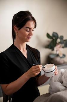 Mulher jovem fazendo tratamento facial em seu cliente Foto gratuita