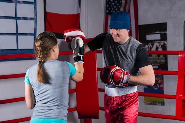 Mulher jovem fazendo treinamento de kickboxing com seu treinador em um ringue de boxe normal em uma academia