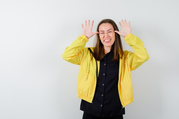 Mulher jovem fazendo um gesto engraçado e parecendo feliz