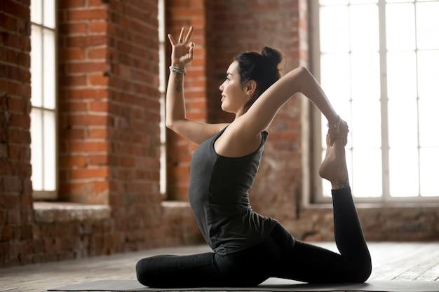 Mulher jovem, fazendo, um, legged, rei, pombo, exercício