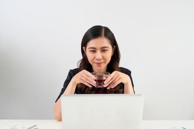 Mulher jovem fazendo uma pausa para o chá enquanto se senta à mesa, trabalhando em um laptop,