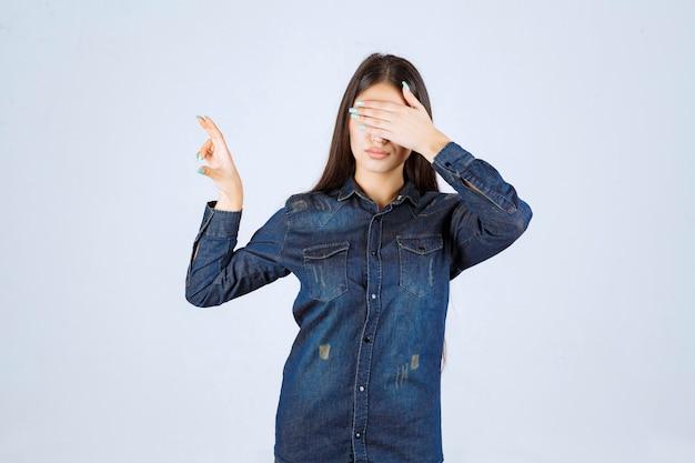 Mulher jovem fechando os olhos ou parte do rosto e olhando por entre os dedos