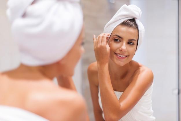 Mulher jovem feliz a pinçar as sobrancelhas