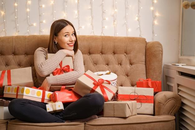 Mulher jovem feliz abraçando muitas caixas de presentes, sentada de pernas cruzadas em um sofá de camelo com luzes
