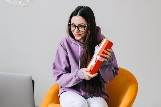 Mulher jovem feliz abrindo o presente na frente do laptop durante a videochamada ou bate-papo, comemorando o aniversário online. conceito de relações à distância, celebrações e estilo de vida.