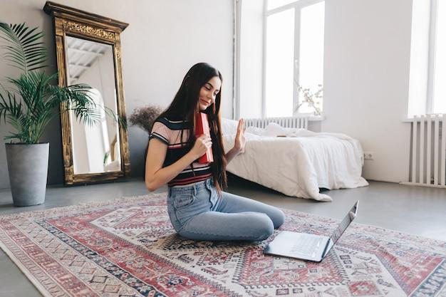 Mulher jovem feliz abrindo o presente na frente do laptop durante a videochamada ou bate-papo, comemorando o aniversário online.
