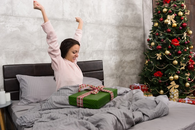 Mulher jovem feliz acorda e se regozija com seu presente de natal enquanto está sentada em uma cama no quarto em estilo loft com árvore de natal com muitos presentes