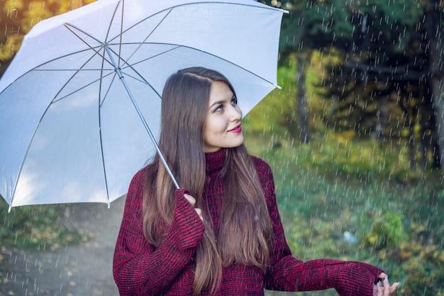 Mulher jovem feliz andando em um parque ensolarado com um guarda-chuva branco na chuva