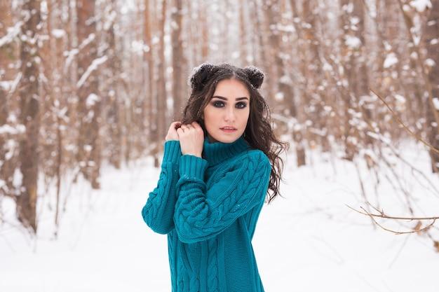 Mulher jovem feliz andando no inverno. menina bonita na natureza de neve