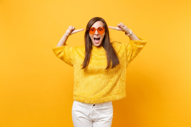 Mulher jovem feliz animada com suéter de pele e óculos coração laranja, apontando o dedo indicador na cabeça isolado em fundo amarelo brilhante. emoções sinceras de pessoas, conceito de estilo de vida. área de publicidade.
