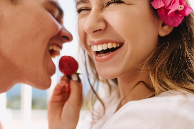 Mulher jovem feliz animada com uma linda flor rosa no cabelo castanho claro, alimentando seu marido sorridente com morango fresco. retrato de close-up de um romântico curtindo a lua de mel e comendo frutas