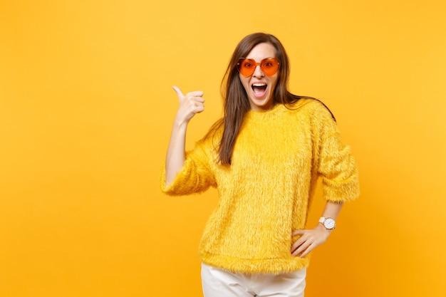 Mulher jovem feliz animada no suéter de pele e óculos coração laranja apontando o polegar de lado no espaço da cópia isolado em fundo amarelo brilhante. emoções sinceras de pessoas, conceito de estilo de vida. área de publicidade.