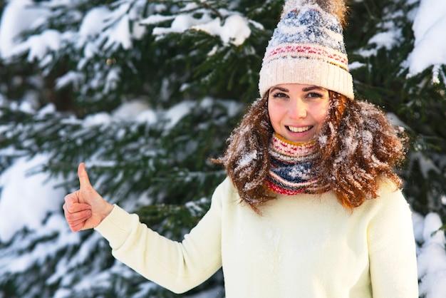 Mulher jovem feliz aparece com o polegar no parque florestal de inverno