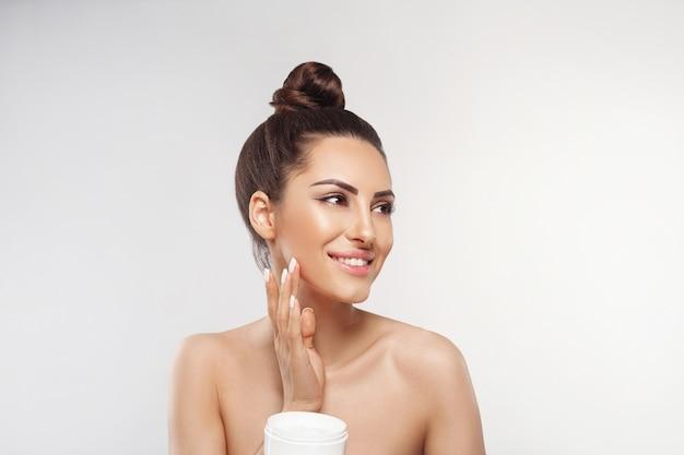 Mulher jovem feliz aplicando creme no rosto conceito de cuidados com a pele e cosméticos