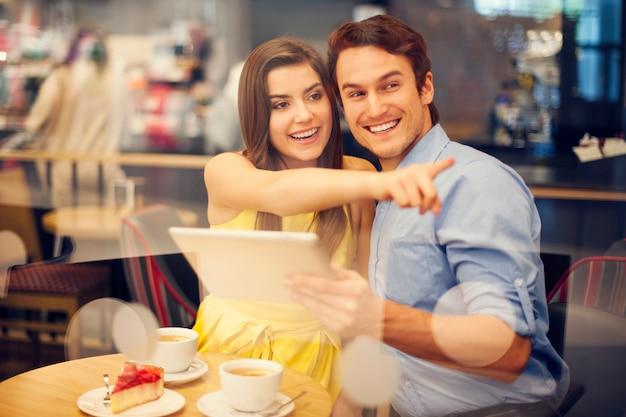 Mulher jovem feliz apontando algo enquanto está sentado no café
