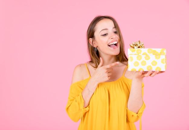 Mulher jovem feliz, apontando o dedo para caixa de presente contra um fundo rosa
