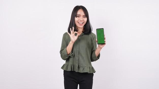 Mulher jovem feliz apontando para um telefone verde com um gesto de ok em uma parede branca isolada