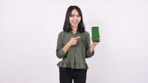Mulher jovem feliz apontando para um telefone verde em uma parede branca e isolada