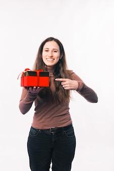 Mulher jovem feliz apontando para uma caixa de presente vermelha