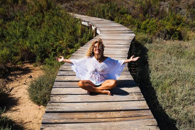 Mulher jovem feliz aproveita as férias de verão, as férias, a atividade de lazer ao ar livre, sentada em um caminho de madeira no parque natural - as pessoas e o estilo de vida de liberdade viajam pelo mundo