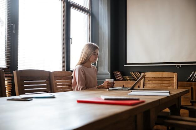 Mulher jovem feliz, bebendo café enquanto trabalhava com o laptop