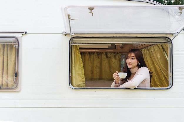 Mulher jovem feliz bebendo café na janela de um trailer trailer van motorhome