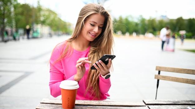 Mulher jovem feliz bebendo um café ao ar livre enquanto usa seu smartphone