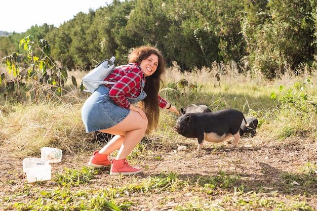 Mulher jovem feliz brinca com pequenos javalis na natureza.