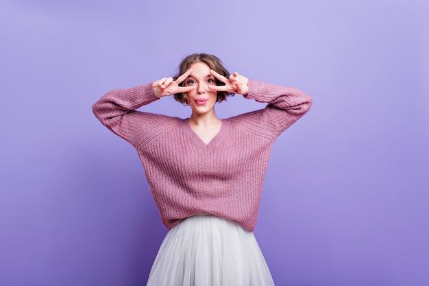 Mulher jovem feliz brincando enquanto posa em um suéter roxo da moda. senhora graciosa com cabelo castanho-escuro fazendo caretas engraçadas durante a sessão de fotos interna