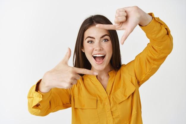 Mulher jovem feliz capturando o momento, fazendo gestos de câmera e sorrindo, em pé sobre uma parede branca