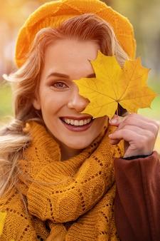 Mulher jovem feliz cobre os olhos com folhas amareladas em uma boina de malha amarela com folhas de outono