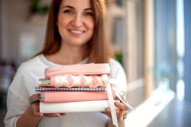 Mulher jovem feliz coletando o diário pessoal e cadernos na papelaria