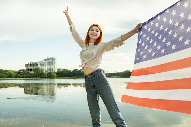 Mulher jovem feliz com a bandeira nacional dos estados unidos na mão