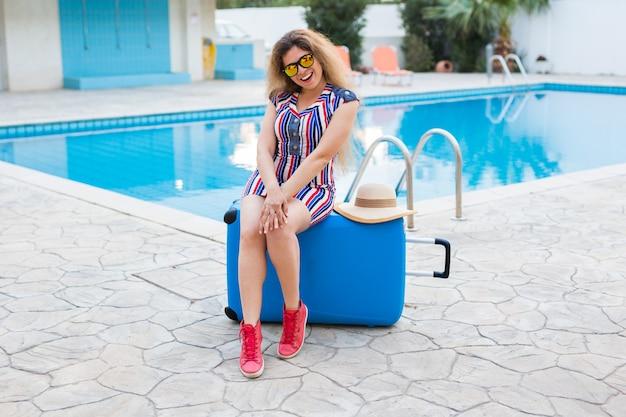 Mulher jovem feliz com bagagem azul chegando ao resort. ela está caminhando ao lado da piscina. início do conceito de férias de verão.