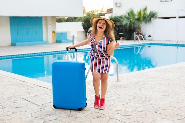 Mulher jovem feliz com bagagem azul chegando ao resort