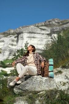 Mulher jovem feliz com cabelo castanho, tendo uma pausa enquanto caminhava com a mochila entre as montanhas rochosas.