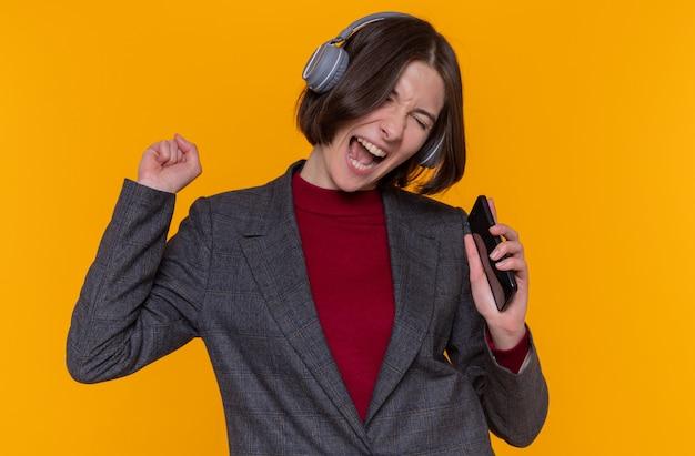 Mulher jovem feliz com cabelo curto, vestindo uma jaqueta cinza com fones de ouvido, curtindo sua música favorita e cantando segurando o smartphone, usando como microfone em pé sobre a parede laranja
