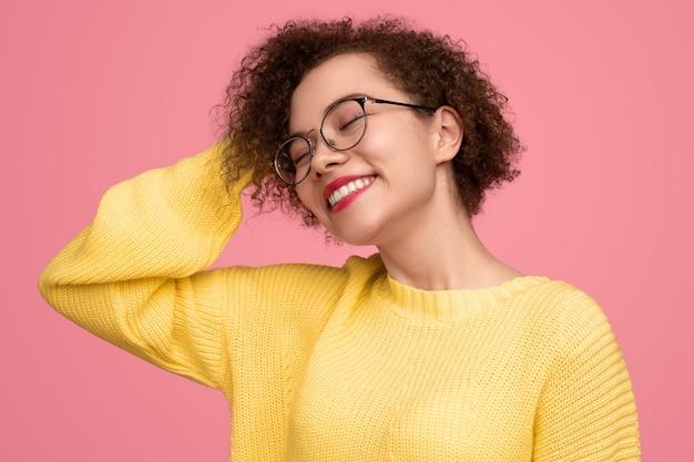 Mulher jovem feliz com cabelo encaracolado e óculos