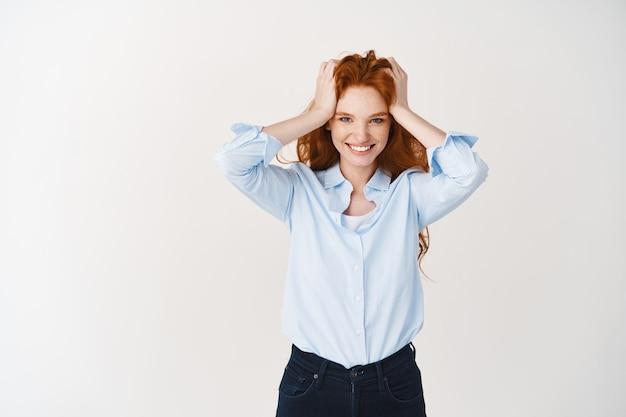 Mulher jovem feliz com cabelo ruivo e sorriso ousado olhando para a frente, tocando a cabeça, em pé sobre uma parede branca