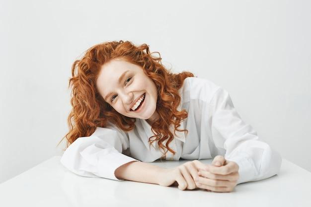 Mulher jovem feliz com cabelo sexy sorrindo sentado à mesa.