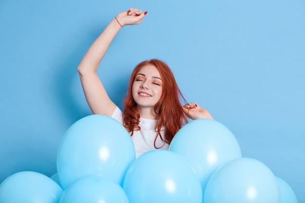 Mulher jovem feliz com cabelo vermelho posando rodeada de balões e dançando com os olhos fechados